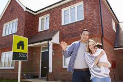 Portrait Of Young Family With Keys To New Home Stock Photos