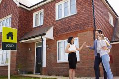 Young Couple Collecting Keys To New Home From Realtor Stock Photos