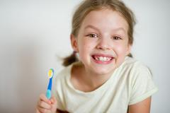 Funny girl with pigtails brushing his teeth. Stock Photos