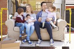 Family With Sofa On Tail Lift Of Removal Truck Moving Home Stock Photos
