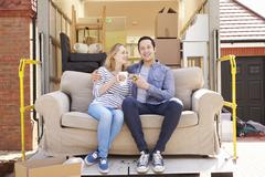 Couple With Sofa On Tail Lift Of Removal Truck Moving Home Stock Photos