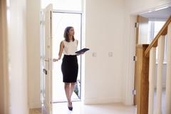 Female Realtor In Hallway Carrying Out Valuation Stock Photos