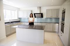 Portrait Of Female Realtor In Kitchen Valuing House Stock Photos