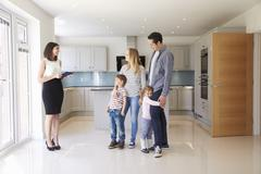 Realtor Showing Young Family Around Property For Sale Stock Photos