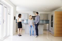 Realtor Showing Young Couple Around Property For Sale Stock Photos