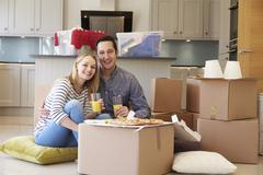 Couple Celebrating Moving Into New Home With Pizza Stock Photos