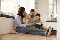 Family Sitting On Floor Reading Story At Home Together Stock Photos