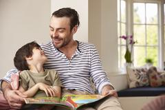 Father And Son Reading Story At Home Together Stock Photos