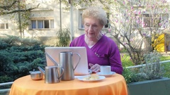 Elder woman using laptop with confidence making breakfast outdoor, light rays Stock Footage