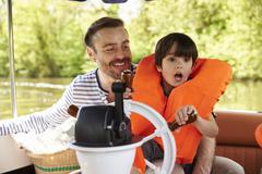 Father And Son Enjoying Day Out In Boat On River Together Stock Photos