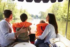 Family Enjoying Day Out In Boat On River Together Stock Photos