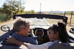 Couple driving in open top car look at each other, back view Stock Photos