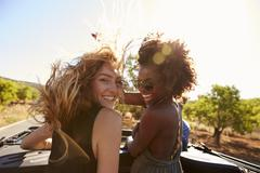 Two women standing in the back of open car turning to camera Stock Photos
