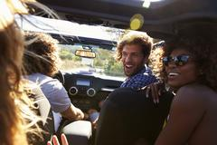 Four friends driving in an open top car, rear passenger POV Stock Photos