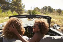 Woman embraces her partner as he drives, rear passenger POV Stock Photos