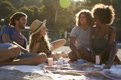 Four friends having a picnic on the beach, lens flare, Ibiza Stock Photos