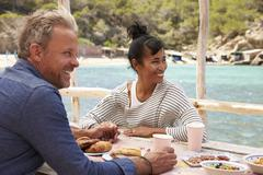 Middle aged couple at table by the sea looking at each other Stock Photos