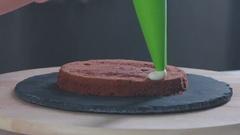 Chocolate cake. Confectioner covers chocolate cake creamy cream Stock Footage