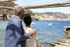 Middle aged couple relaxing on a jetty by the sea, Ibiza Stock Photos