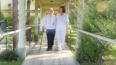 Asian nurse helping elder woman with stick in hospital garden, light rays coming Stock Footage