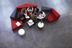 Overhead Shot Of Businesswomen Meeting In Lobby Of Office Stock Photos