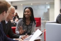 Businesspeople Discuss Document In Lobby Of Modern Office Stock Photos