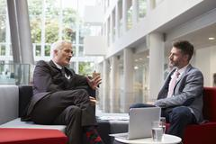 Two Businessmen Meeting In Lobby Area Of Modern Office Stock Photos