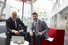 Portrait Of Businessmen Meeting In Lobby Of Modern Office Stock Photos