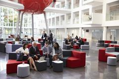 Businesspeople Meeting In Busy Lobby Of Modern Office Stock Photos