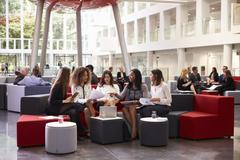 Businesswomen Meeting In Busy Lobby Of Modern Office Stock Photos