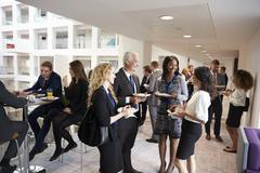 Delegates Networking During Conference Lunch Break Stock Photos