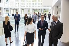 Businesspeople In Busy Lobby Area Of Modern Office Stock Photos