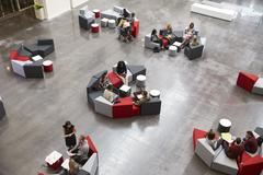 Students sit in groups in a modern university atrium Stock Photos