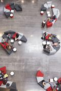 Students groups sit in a modern university atrium, vertical Stock Photos