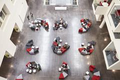 Student groups on seating in a modern university atrium Stock Photos