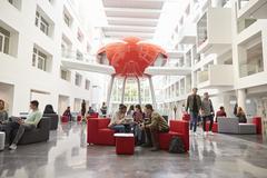 Students socialising in the lobby of modern university Stock Photos