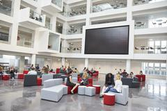 Students meeting in front of screen in atrium at university Stock Photos