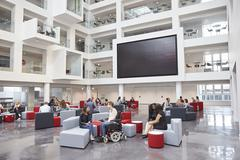 Students socialising under AV screen in atrium at university Stock Photos