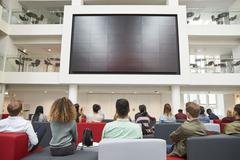 Students watching big screen in university atrium, back view Stock Photos