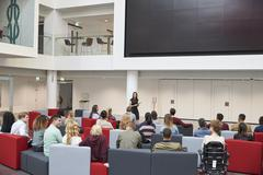 Students at a lecture in university atrium, back view Stock Photos