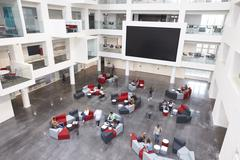 Modern university lobby atrium and glass fronted study rooms Stock Photos
