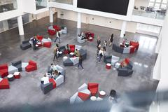 Busy university atrium area, seen from an indoor balcony Stock Photos