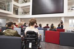 Back view of students at a lecture in a university atrium Stock Photos