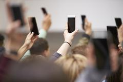 Hands in a crowd holding phones up to take pictures Stock Photos
