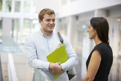 Adult student and teacher talking in university foyer Stock Photos