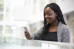 Young black female student using phone in university foyer Stock Photos