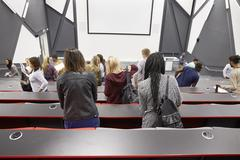 Students leaving university lecture theatre, back view Stock Photos