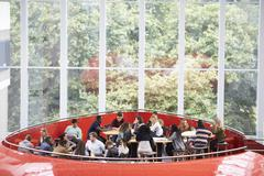 Students hanging out in university mezzanine social area Stock Photos