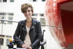 Smiling disabled female university student on mezzanine Stock Photos