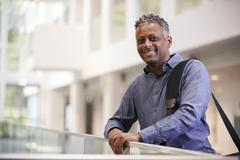 Middle aged black man smiling in modern building lobby Stock Photos